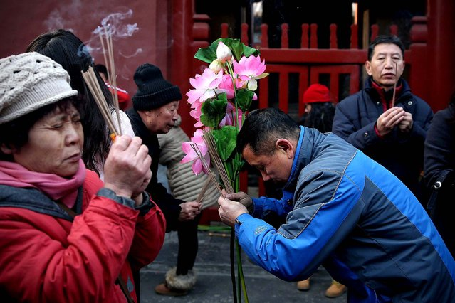 People pray for good fortune as they hold burning incense on the first day of the Chinese Lunar New Year at Yonghegong Lama Temple in Beijing. (Photo by Feng Li/Getty Images)