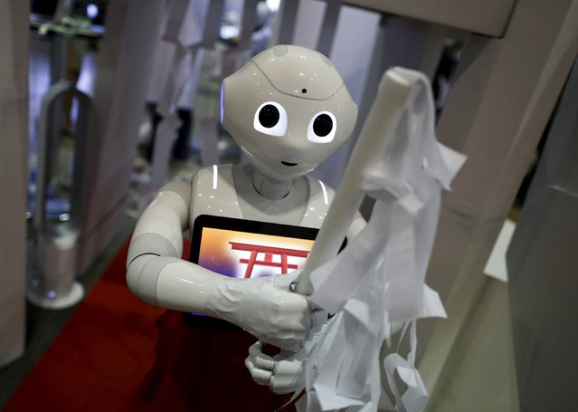 "SoftBank Corp's humanoid robot named ""Pepper"", dressed as a shrine maiden, ""purifies"" visitors at a booth during ""Niconico Chokaigi 2015"" in Makuhari, east of Tokyo, Japan April 26, 2015. About 150,000 people visited more than 100 booths of Japan's subcultures made through Niconico, Japan's youtube-like internet video sharing web portal, at its two-day annual offline fan meeting called ""Niconico Chokaigi 2015"". (Photo by Yuya Shino/Reuters)"