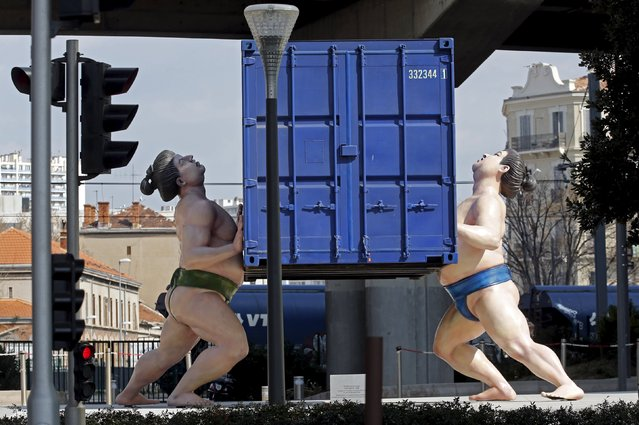 "The sculpture ""It Takes Two to Tango"" by Scottish sculptor David Mach is seen in front of the headquarters of the CMA-CGM shipping company office tower in the port of Marseille, France, March 15, 2016. (Photo by Jean-Paul Pelissier/Reuters)"