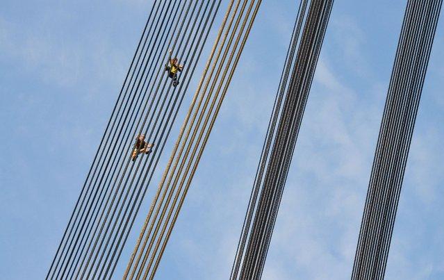 Yaroslav Segeda and his friends climb the Moscow Bridge in Kiev. (Photo by Yaroslav Segeda/Solent News)
