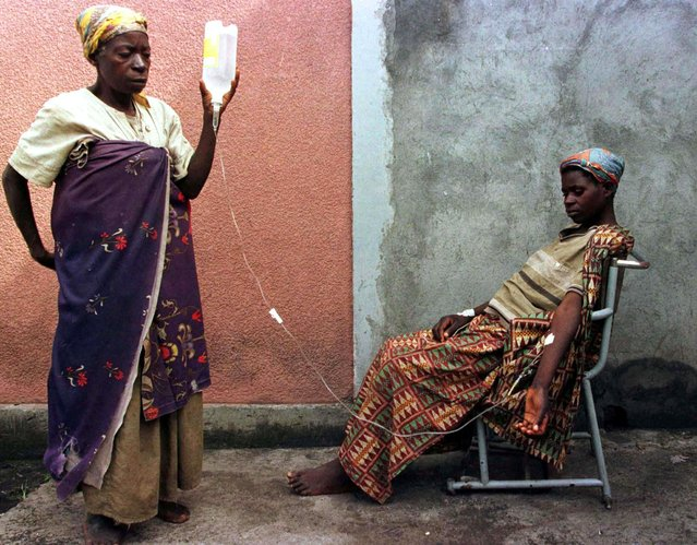 A Rwandan Hutu refugee woman helps her daughter with an IV at the local hospital in the town of Goma in the former Zaire, now the Democratic Republic of the Congo, November 17, 1996. (Photo by John Parkin/Reuters)
