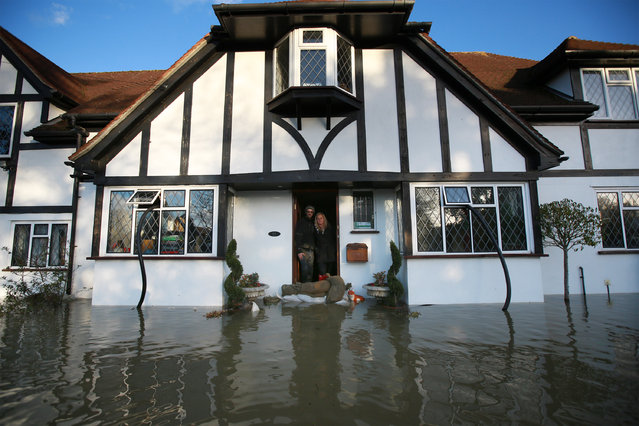 Resident Ian Grey stands in his doorway with his sister Laura Grey surrounded by floodwater on February 11, 2014 in Wraysbury, England. The Environment Agency has issued severe flood warnings for a number of areas on the river Thames west of London. (Photo by Peter Macdiarmid/Getty Images)