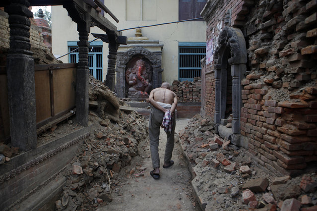 An elderly Nepalese walks past a damaged temple performing rituals to end the mourning period of a family member who died in the April 25 earthquake, in Bhaktapur, Nepal, Wednesday, May 6, 2015. (Photo by Niranjan Shrestha/AP Photo)