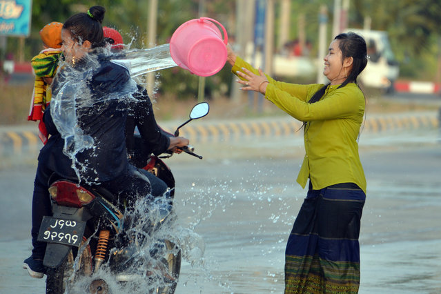 A woman throws water at passing motorists during celebrations for the Thingyan festival, also known as the Buddhist New Year, in Naypyidaw, Myanmar on April 16, 2019. (Photo by Thet Aung/AFP Photo)