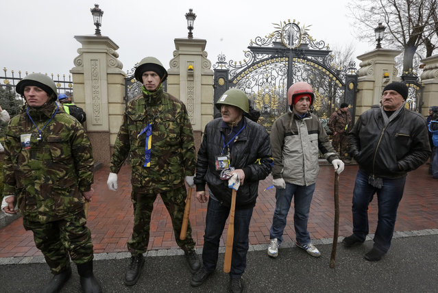 Anti-government protesters stand guard by the entrance to the Mezhyhirya residence of Ukraine's President Viktor Yanukovich in the village Novi Petrivtsi, outside Kiev February 22, 2014. (Photo by Konstantin Chernichkin/Reuters)