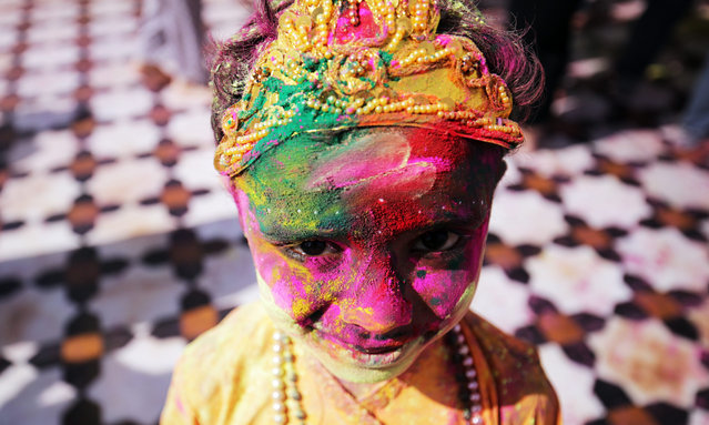 An Indian child smeared in colors and dressed as a Hindu God, Lord Krishna poses for a photograph during the Holi festival celebrations at Sri Laxmi Narayan Temple in Amritsar, India, 23 March 2016. Holi is celebrated at the end of the winter season on the last full moon day of the lunar month Phalguna (February or March) which usually falls in the later part of February or March and is celebrated by people throwing colored powder and colored water at each other. (Photo by Raminder Pal Singh/EPA)