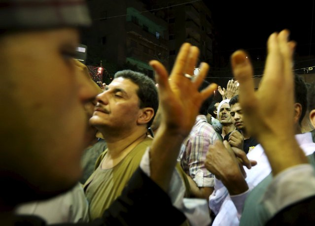 Egyptians dance to the music of a Sufi singer as they celebrate the birthday of Sayida Zeinab, the granddaughter of Prophet Mohammad, near her shrine in Cairo, May 13, 2015. (Photo by Mohamed Abd El Ghany/Reuters)