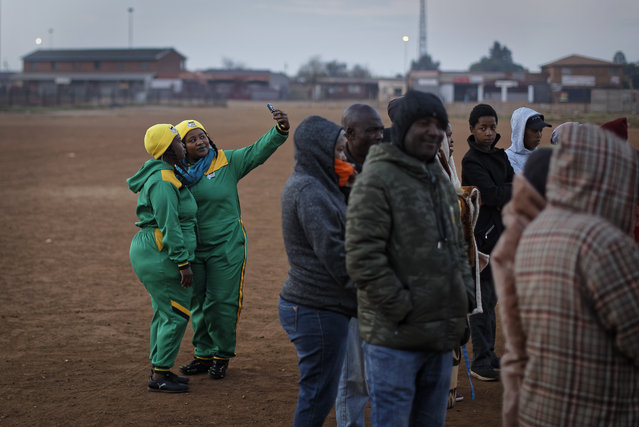 Two supporters of the African National Congress (ANC) take selfies as they queue in the early morning cold to cast their votes in the mining settlement of Bekkersdal, west of Johannesburg, in South Africa Wednesday, May 8, 2019. South Africans are voting Wednesday in a national election that pits President Cyril Ramaphosa's ruling African National Congress against top opposition parties Democratic Alliance and Economic Freedom Fighters, 25 years after the end of apartheid. (Photo by Ben Curtis/AP Photo)