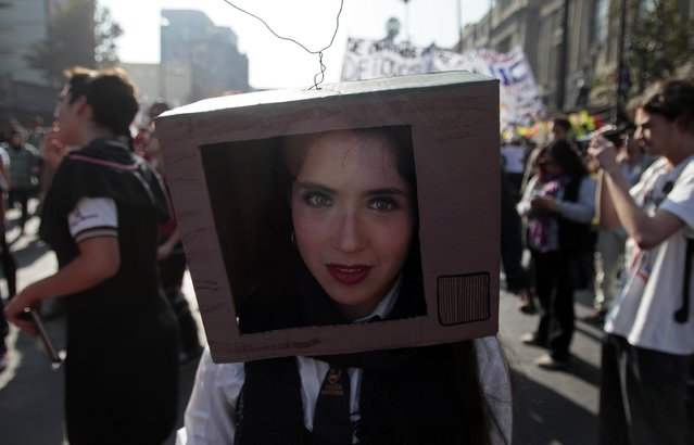 A demonstrator marches with a cardboard box on her  head during a march for free education, in Santiago, Chile, Thursday, May 14, 2015. (Photo by Luis Hidalgo/AP Photo)