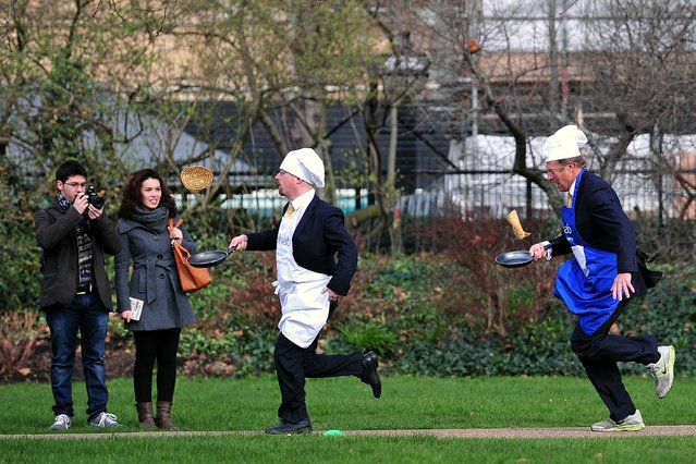 British parliamentarians Lord St John of Bletso (R) and Julian Huppert MP (2nd R) take part in the annual parliamentary pancake race on Shrove Tuesday in central London on March 4, 2014. (Photo by Carl Court/AFP Photo)