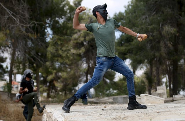 "A Palestinian protester throws a stone towards Israeli troops during clashes following a rally marking Nakba Day near Israel's Ofer Prison near the West Bank city of Ramallah May 15, 2015. Palestinians mark ""Nakba"" (Catastrophe) on Friday to commemorate the expulsion or fleeing of some 700,000 Palestinians from their homes in the war that led to the founding of Israel in 1948. (Photo by Mohamad Torokman/Reuters)"