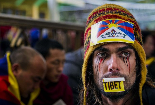 Austrian national Maximilian with a Tibetan flag attached to his hat joins exiled Tibetans at a gathering to mark the 55th anniversary of the failed uprising in the Tibetan capital Lhasa in 1959, in Dharmsala, India, on March 10, 2014. The uprising of the Tibetan people against the Chinese rule was brutally quelled by Chinese army forcing the spiritual leader the Dalai Lama and hundreds of Tibetans to come into exile. (Photo by Ashwini Bhatia/Associated Press)