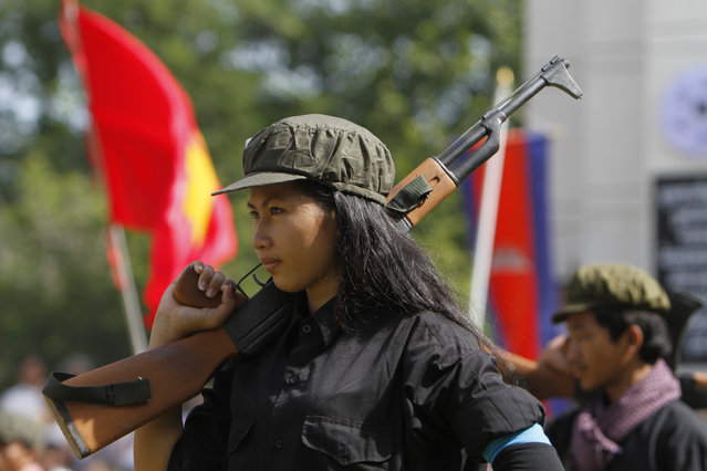 "A Cambodian student of Royal University of Fine Arts performs during a reenactment of torture and execution committed by the Khmer Rouge during their reign of terror in the 1970s to mark the annual Day of Anger at Choeung Ek, a former Khmer Rouge ""killing field"", on the outskirt of Phnom Penh, Cambodia Wednesday, May 20, 2015. Cambodia on Wednesday marked the 36th anniversary of the Day of Anger to remember the atrocities committed during the Khmer Rouge's 1975-79 era. (Photo by Heng Sinith/AP Photo)"