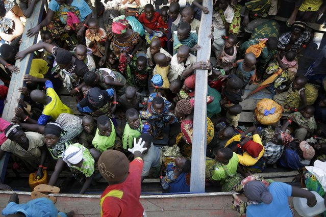 Refugees who fled Burundi's violence and political tension wait in a speedboat to board a ship freighted by the UN, at Kagunga on Lake Tanganyika, Tanzania, Saturday, May 23, 2015 to be taken to the port city of Kigoma. An outbreak of cholera has infected 3,000 people in a Tanzanian border region where refugees fleeing political unrest in Burundi have massed, the U.N. Refugee Agency said Friday, May 22, 2015. (Photo by Jerome Delay/AP Photo)