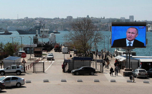 People walk under an electronic screen showing nationwide call-in attended by Russian President Vladimir Putin on a street of the Black Sea port of Sevastopol, Crimea, April 14, 2016. (Photo by Pavel Rebrov/Reuters)
