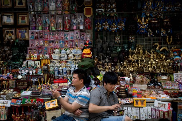 Vendors browse their smartphones as they wait for customer at their store selling Chinese made souvenirs at the Wangfujing shopping district in Beijing, China Thursday, May 21, 2015. Manufacturing in China shrank for the third straight month in May as demand remained soft, raising the chances of more stimulus to prop up growth in the world's No. 2 economy. (Photo by Andy Wong/AP Photo)