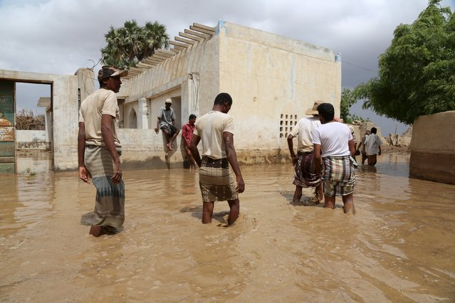 People wade through a flooded neighborhood following heavy rain in a village in Yemen's Red Sea province of Houdieda April 15, 2016. (Photo by Abduljabbar Zeyad/Reuters)