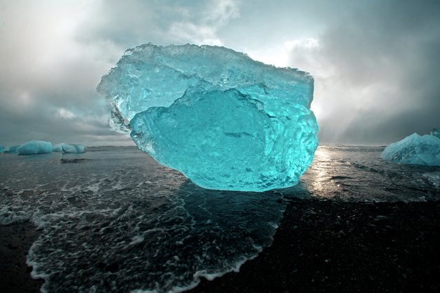 """""""Iceberg Gallery"""". Like a scene from a different time on earth, or a completely different planet altogether. Passed down through Jökulsárlón lagoon through an outlet of the Vatnajökull Glacier, Icebergs enter into the North Atlantic. (Photo and caption by Sam Morris/National Geographic Traveler Photo Contest)"""