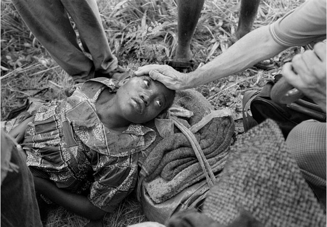 A Rwandan refugee lies moaning on a path in the bush as a priest and a member of Doctors Without Borders comfort her. She was gravely ill with malaria; 1996. (Photo by Carol Guzy/The Washington Post)