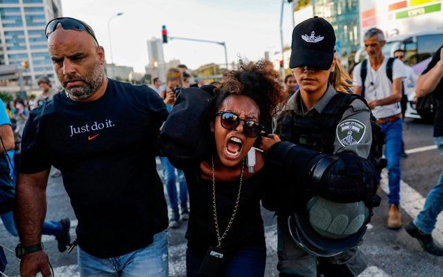 Members of the Israeli security forces detain a protester during a demonstration in Tel Aviv on July 3, 2019, against police violence and the recent killing of a young man. Israel braced for a third day of protests after an off-duty police officer killed a young man of Ethiopian origin, as Israeli leaders urged calm amid accusations of racism. In areas throughout the country since July 1, protesters have blocked roads, burned tyres and denounced what they see as discrimination against the Ethiopian-Israeli community. Police say 136 people have been arrested and 111 officers have been wounded, many injured by stones, bottles and petrol bombs thrown at them. (Photo by Ahmad Gharabli/AFP Photo)