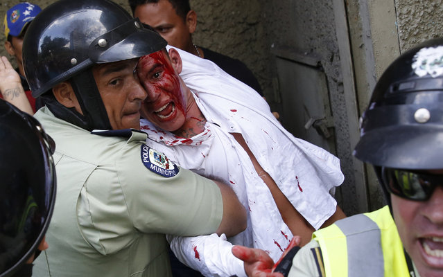 Police protect a man from being hurt by anti-government protesters who accuse him of being a government spy, during an anti-government demonstration in Caracas April 4, 2014. (Photo by Carlos Garcia Rawlins/Reuters)