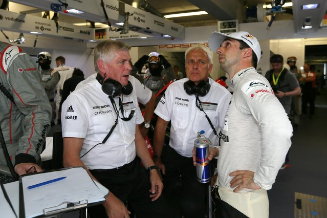 Swiss driver Neel Jani, right, talks with team's members during the 83rd 24-hour Le Mans endurance race, in Le Mans, western France, Saturday, June 13, 2015. (AP Photo/David Vincent)