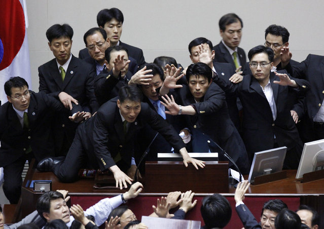 Lee Yoon-sung (C), vice speaker of the National Assembly and a lawmaker of the ruling Grand National Party, is surrounded by security guards as he passes new bills at the National Assembly main chamber in Seoul July 22, 2009. (Photo by Jo Yong-Hak/Reuters)