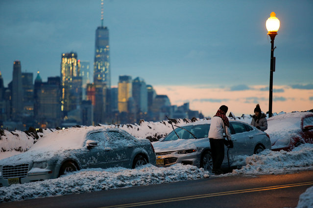 Residents clear their cars and street of snow in Weehawken, New Jersey, as the One World Trade Center and lower Manhattan are seen after a snowstorm in New York, U.S., March 15, 2017. (Photo by Eduardo Munoz/Reuters)