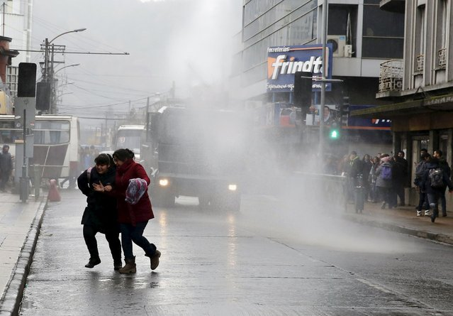 Students run away from a jet of water from a riot police water cannon during a demonstration for education reform, in Temuco, June 25, 2015. (Photo by Andres Stapff/Reuters)