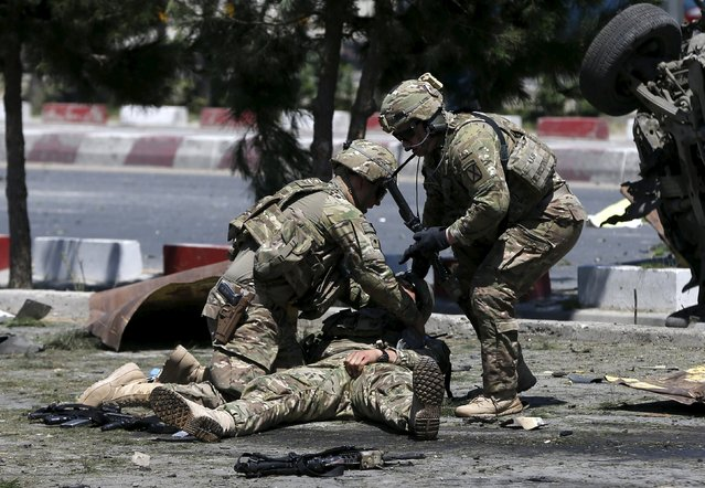 U.S. soldiers attend to a wounded soldier at the site of a blast in Kabul, Afghanistan June 30, 2015. (Photo by Omar Sobhani/Reuters)