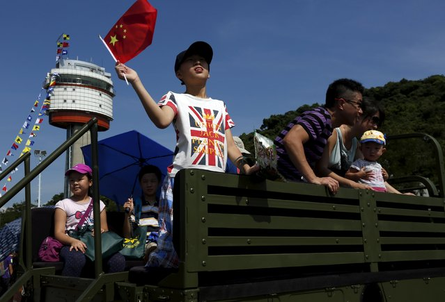 A visitor waves a Chinese national flag while wearing a t-shirt featuring a British flag, on a military vehicle at a People's Liberation Army naval base in Hong Kong July 1, 2015. Wednesday marks the 18th anniversary of Hong Kong's handover from Britain to Chinese sovereignty. (Photo by Bobby Yip/Reuters)