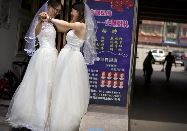 Teresa Xu, left, and Li Tingting, right, share an intimate moment outside of a beauty salon where the two were preparing for their wedding in Beijing, Thursday, July 2, 2015. (Photo by Mark Schiefelbein/AP Photo)