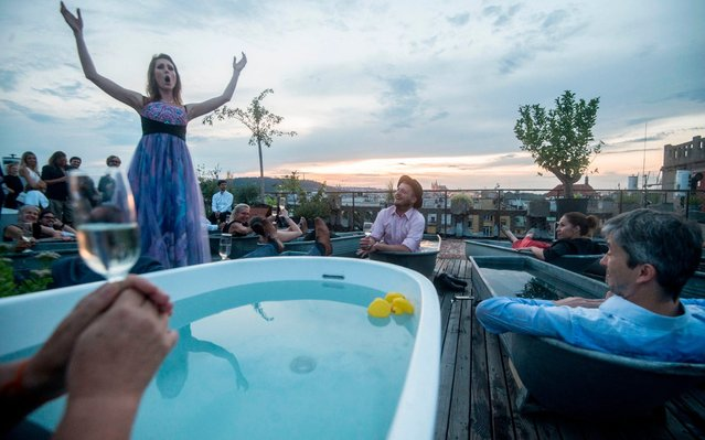 Spectators in bathtubs listen Czech opera singer Eva Kyvalova performing parts of Mozart's Don Giovanni, at the rooftop of Lucerna Palace building on August 29, 2019 in Prague. (Photo by Michal Cizek/AFP Photo)