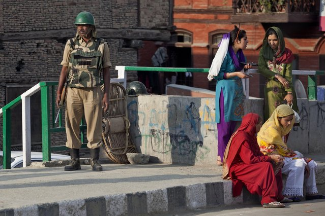An Indian paramilitary solider stands guard as Kashmiri Muslim women wait for a bus in Srinagar, Indian controlled Kashmir, Wednesday, July 1, 2015. The wide-ranging powers granted to Indian soldiers in Kashmir have fuelled a cycle of impunity for human rights violations in the troubled Himalayan region, Amnesty International said Wednesday. (Photo by Dar Yasin/AP Photo)