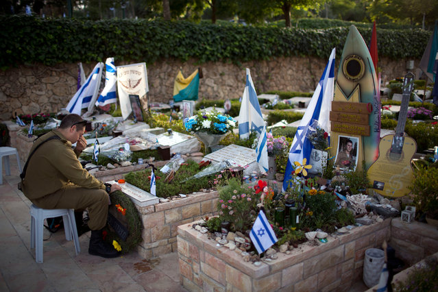 An Israeli soldier visits the grave of his friend on the Memorial Day eve commemorating fallen soldiers, at the military cemetery at Mount Hertzl in Jerusalem, Tuesday, May 10, 2016. (Photo by Oded Balilty/AP Photo)