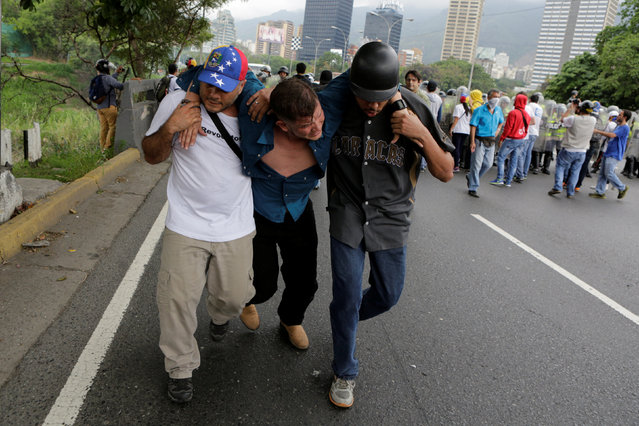 Opposition supporters carry an injured man during clashes with riot policemen in a rally to demand a referendum to remove President Nicolas Maduro in Caracas, Venezuela, May 11, 2016. (Photo by Marco Bello/Reuters)