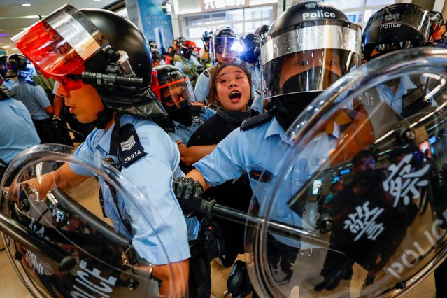 Riot police detain a woman as anti-government protesters gather at Sha Tin Mass Transit Railway (MTR) station to demonstrate against the railway operator, which they accuse of helping the government, in Hong Kong, China on September 25, 2019. (Photo by Tyrone Siu/Reuters)