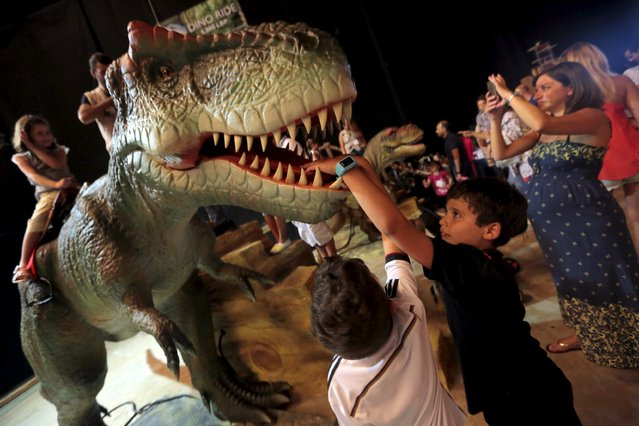Children look at a dinosaur statue during a dinosaur-themed exhibition in Beirut, Lebanon, July 11, 2015. (Photo by Jamal Saidi/Reuters)