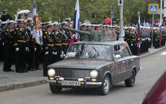 "A Soviet-era car with a sign ""Seventy years without war"" drives past during a Victory Day military parade in Sevastopol, Crimea, Friday, May 9, 2014. Russian President Vladimir Putin extolled the return of Crimea to Russia before tens of thousands Friday during his first trip to Black Sea peninsula since its annexation. The triumphant visit was quickly condemned by Ukraine and NATO. (Photo by Ivan Sekretarev/AP Photo)"