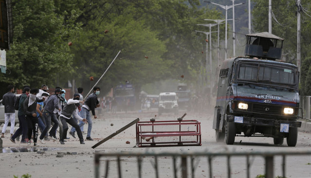 Kashmiri students and other protesters throw stones at an Indian police vehicle as they clash in Srinagar, Indian controlled Kashmir, Monday, April 24, 2017. (Photo by Mukhtar Khan/AP Photo)