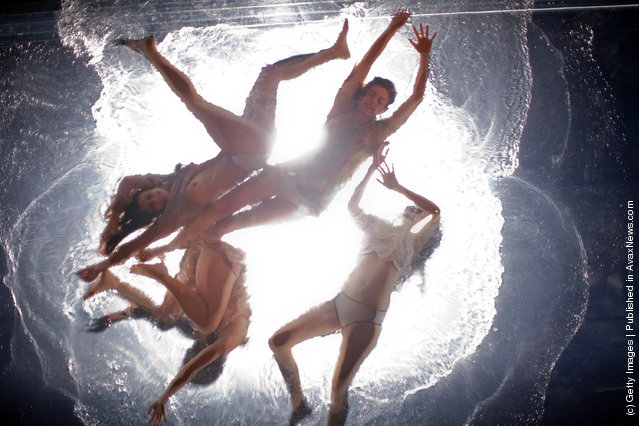 Artists preform on a pool suspended above the audience during the Fuerza Bruta dress rehearsal