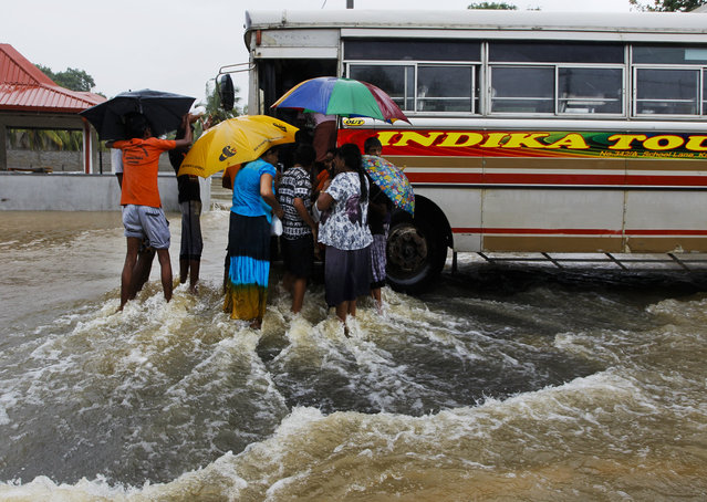 Sri Lankan flood victims flock around a bus to receive food parcels on a inundated road in Colombo, Sri Lanka, Tuesday, May 17, 2016. The Disaster Management Center said that 114 homes have been destroyed and more than 137,000 people have been evacuated to safe locations as heavy rains continue. (Photo by Eranga Jayawardena/AP Photo)