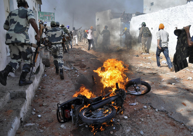 A motorcycle set on fire by a mob burns during clashes between two communities on the outskirts of the southern Indian city of Hyderabad May 14, 2014. Two people were killed when police opened fire to control mobs following communal clashes on Wednesday on the outskirts of the city, local media reported. (Photo by Reuters)