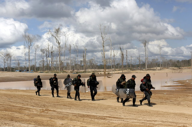 Peruvian police officers take part in an operation to destroy illegal gold mining camps in a zone known as Mega 14, in the southern Amazon region of Madre de Dios July 13, 2015. (Photo by Janine Costa/Reuters)
