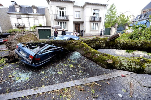 People walk by a car destroyed by a tree which fell during a storm and strong winds, in Limoges, on May 21, 2014. High winds upto 120 km/h and storms have caused at least one death and cut off some 42 000 homes from electricity today in the Midi-Pyrenees region of France. (Photo by Pascal Lachenaud/AFP Photo)