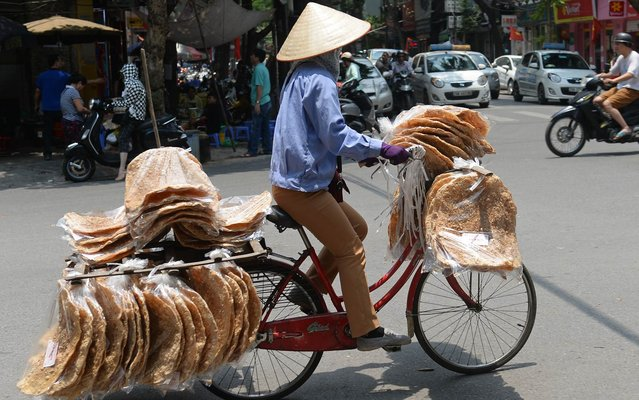"A street vendor sells ""banh da"" (rice crackers) carried on her bicycle in downtown Hanoi on May 17, 2016. (Photo by Hoang Dinh Nam/AFP Photo)"