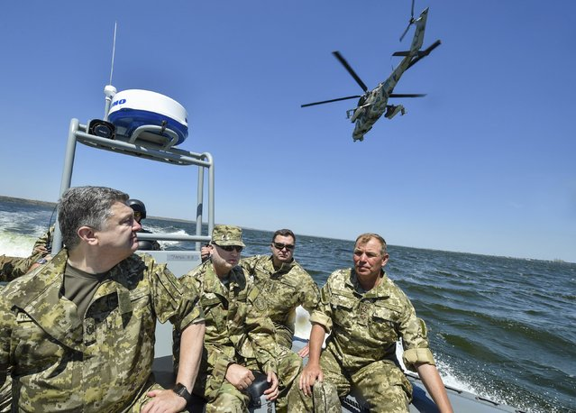 Ukraine's President Petro Poroshenko (L) inspects a military drill with the Secretary of the National Security and Defense Council of Ukraine Oleksandr Turchynov (2nd L), in the waters of the Black Sea in Mykolaiv region, Ukraine, July 21, 2015. (Photo by Mykola Lazarenko/Reuters/Ukrainian Presidential Press Service)