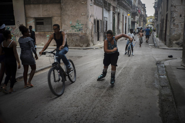 In this November 9, 2019 photo, a youth rollerblades amid cyclists and pedestrians in Old Havana, Cuba. (Photo by Ramon Espinosa/AP Photo)