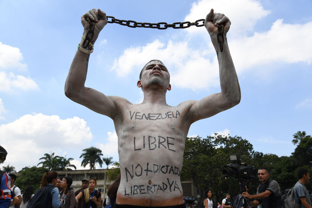 A university student holds a chain with his body painted during a protest against Venezuela's President Nicolas Maduro in Caracas on November 21, 2019. (Photo by Yuri Cortez/AFP Photo)