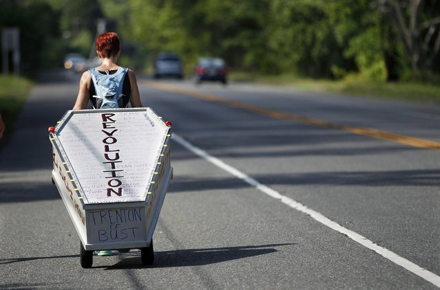 Greta Schwartz, of Seaville, N.J., pulls a casket as she walks along route 206, from southern New Jersey to Trenton Tuesday, May 31, 2016, in Tabernacle, N.J. Schwartz got the idea for the walk after attending a discussion on mental health, addiction and suicide from former U.S. Rep. Patrick Kennedy last year. The casket bears the names of about 70 people Schwartz had a personal connection to who have committed suicide. (Photo by Mel Evans/AP Photo)